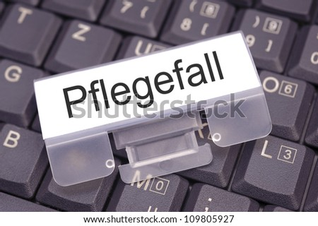 paper on keyboard marked with Pflegefall - nursing case