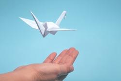 Paper origami bird over hand
