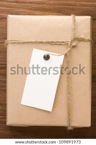 paper parcel wrapped tied with price tag on wood background