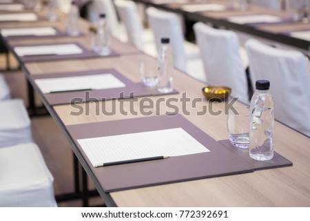 Paper, pencil, water bottle, glass on the table in the seminar room background #772392691