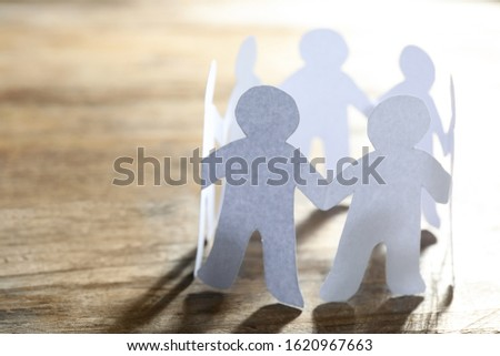 Paper people chain making circle on wooden background, space for text. Unity concept