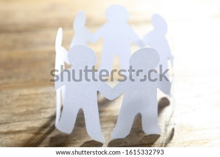 Paper people chain making circle on wooden background. Unity concept