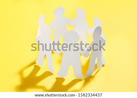 Paper people chain making circle on yellow background. Unity concept #1582334437