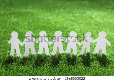 Paper people chain on green grass. Unity concept