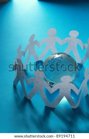Paper people standing around globe holding hands.
