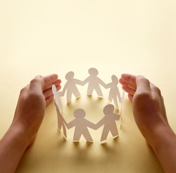 Paper people surrounded by hands in gesture of protection. Concept of insurance, social protection and support.