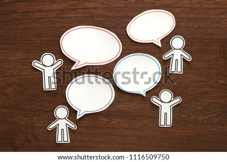 Paper people  with colorful blank dialog speech bubbles on brown wood.  Communication concept.