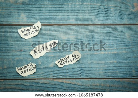Paper pieces with phrases about autism on wooden background #1065187478