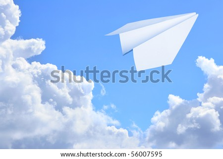 Paper plane flying against sky and clouds in the background - stock photo