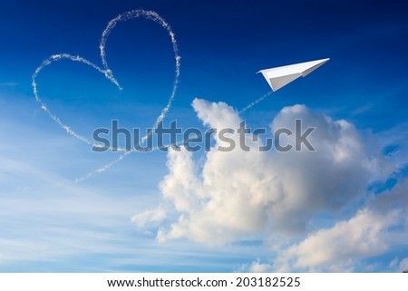 Paper plane flying with the heart shape in the sky