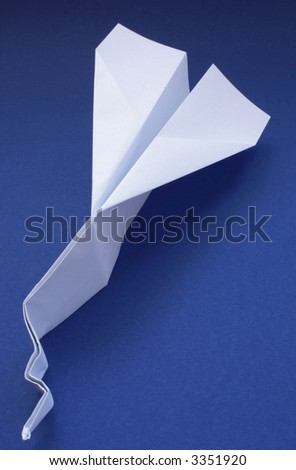 Paper plane with damaged nose on blue background; concepts: crash, failure, business failure
