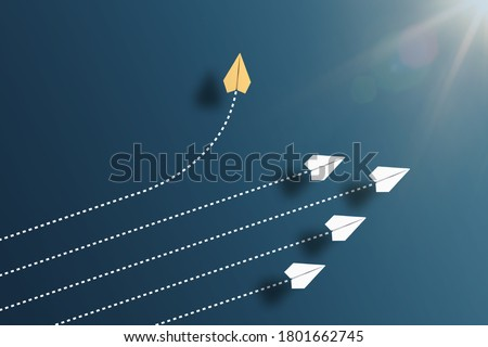 paper planes flying in formation in one direction on blue background and one paper glider going in different direction, breaking new ground and stepping out of the line concept Stock photo ©