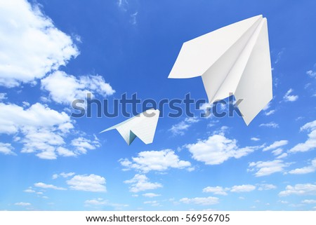 Paper planes flying. Sky and clouds in the background