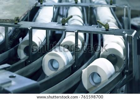 Paper plant, paper tissue rolls on conveyor line. Closeup. Motion blur. Selective focus.