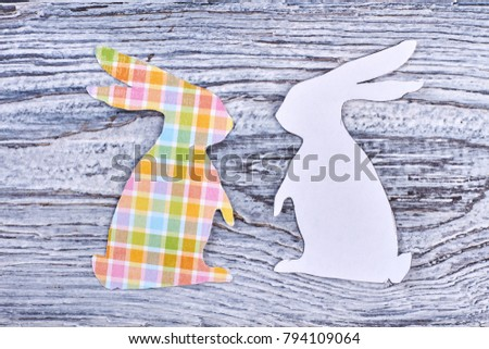 Paper rabbit cutouts, top view. Couple of white and patterned Easter bunnies on rustic wooden background. Papercut animalistic silhouettes for Easter holidays. #794109064