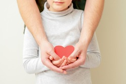 Paper red heart in hands of male dad and little child girl on yellow background at home.