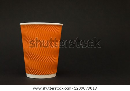 paper reflow orange coffee cup stands on a black background