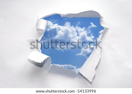 Paper ripped to reveal blue sky.