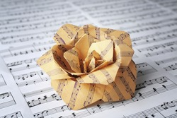 Paper rose on music notes