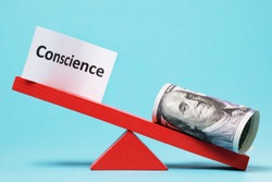 Paper sheet and money on a swing. The concept of conscience