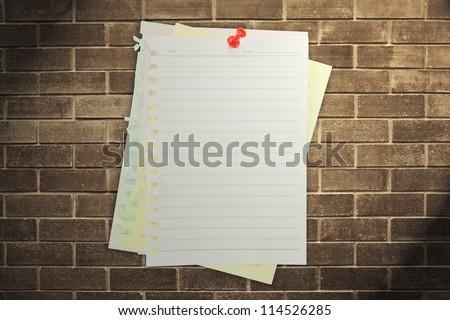 paper sheet and red pin on dark brick wall