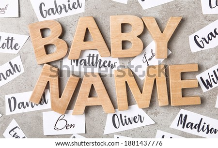 Paper sheets with different baby names and wooden letters on grey background, flat lay Foto d'archivio ©