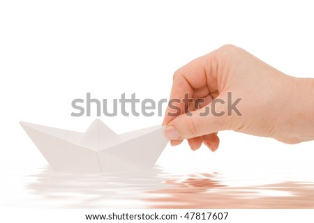 Paper ship in a female hand - stock photo