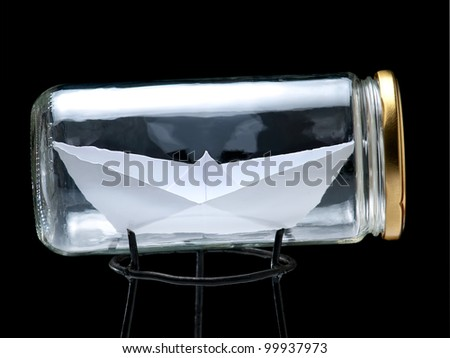 Paper ship in the jar on a black background.