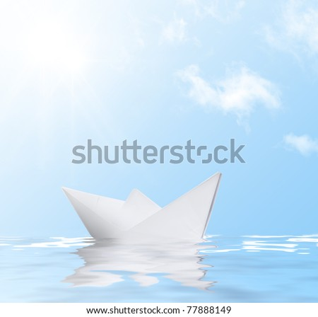 Paper ship in water with reflection against blue sunny sky