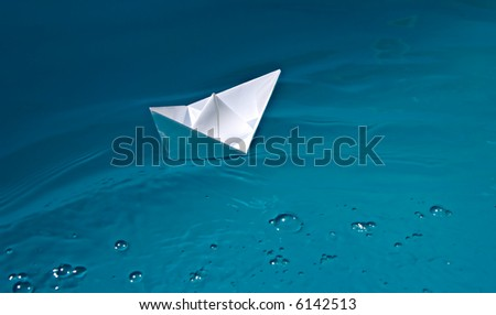 paper ship on blue waves