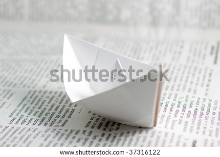 Paper ship over a newspaper