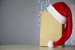 Paper shopping bag and Santa hat with Christmas lights on background and free place for your text on gray. Holidays shopping, discounts and promotion, Christmas delivery service concept Copy space.