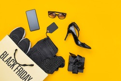 Paper shopping bag with clothes spill out on yellow background. Black friday concept. Top view, flat lay