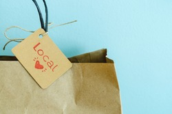 Paper shopping bag with label on blue background. Label with heart and text LOCAL. Shopping concept. Copy space.