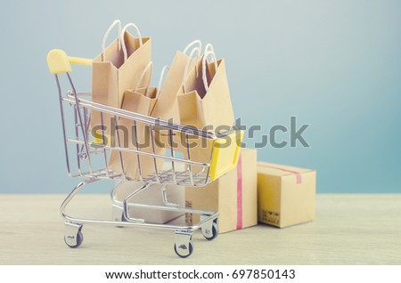 Paper shopping bags  in a shopping cart on wood table,on blue wall background.concept online shopping. #697850143