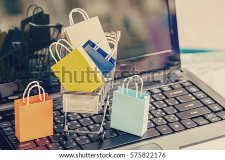 Paper shopping bags in a trolley. Ideas about online shopping addiction, it is a deficiency of impulse control which appears as the eagerness for constantly making new purchase of unnecessary things.