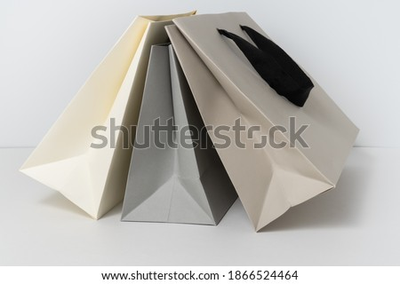 Paper shopping bags in neutral colors on white background. Fashion shopping concept. Photo stock ©