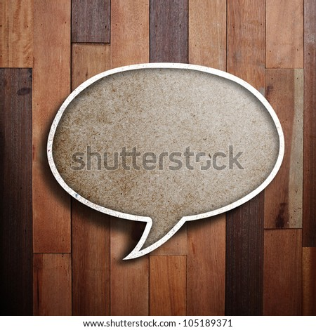 paper speech bubble on wood background.