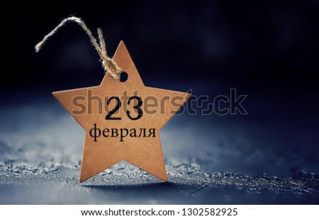 Paper star with inscription on February 23. February 23 Holiday background. Fatherland defender day. men's day of defenders in Russia, Belarus,Tajikistan and Kyrgyzstan. Kraft paper star label on dark