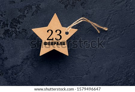 Paper star with inscription on February 23. February 23 Holiday background. Fatherland defender day. men's day of defenders in Russia, Belarus,Tajikistan, Kyrgyzstan. Kraft paper star on dark template