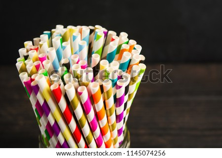Paper straw of different colors on dark background with copy space