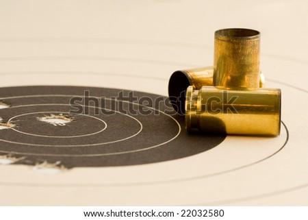 Paper target with bulls eye shot from a 40 caliber handgun, empty bullet cartridges shown.