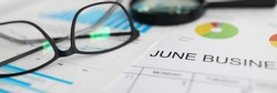 Paper timetable for june lying at workplace among charts and other important documents close-up