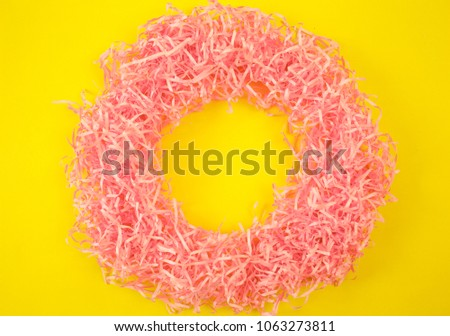 Paper tinsel on a yellow background. The toy is decorative. Decorative background #1063273811