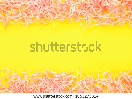 Paper tinsel on a yellow background. The toy is decorative. Decorative background #1063273814