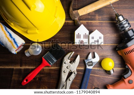 Paper white house toy and construction tools on wooden background with copy space.Real estate concept, New house concept, Finance loan business concept, Repair maintenance concept.