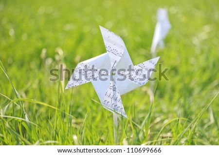 paper windmill in green grass field