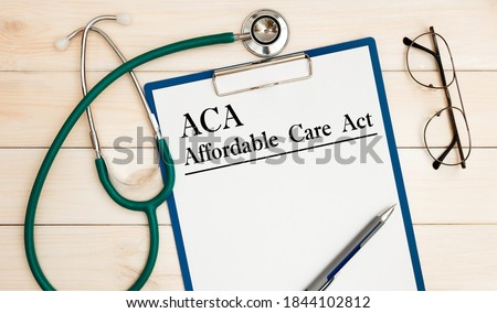 Paper with ACA Affordable Care Act on the office table, calculator and stethoscope. Medical concept. Imagine de stoc ©