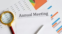 Paper with Annual Meeting on the table with pen