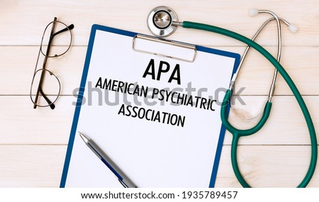 Paper with APA American Psychiatric Association on the office desk, stethoscope and glasses, top view Stok fotoğraf ©